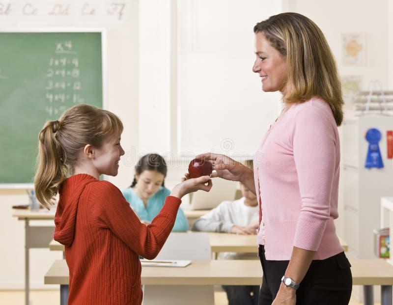 Estudiante que da la manzana del profesor fotografía de archivo
