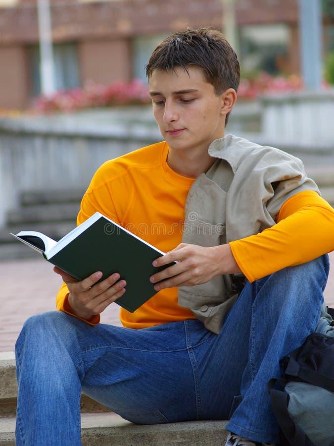 Estudiante que estudia con la chaqueta a través de un hombro imagen de archivo
