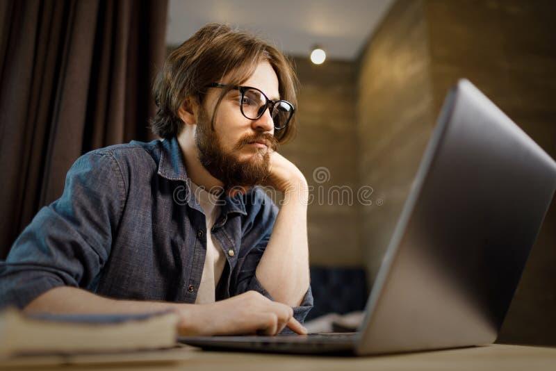 Estudiante que estudia con la computadora port?til imagenes de archivo