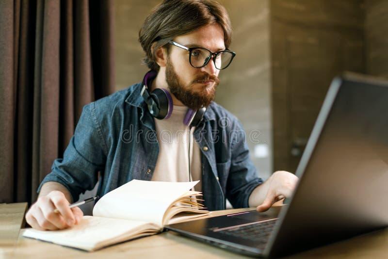 Estudiante que estudia con la computadora port?til foto de archivo libre de regalías