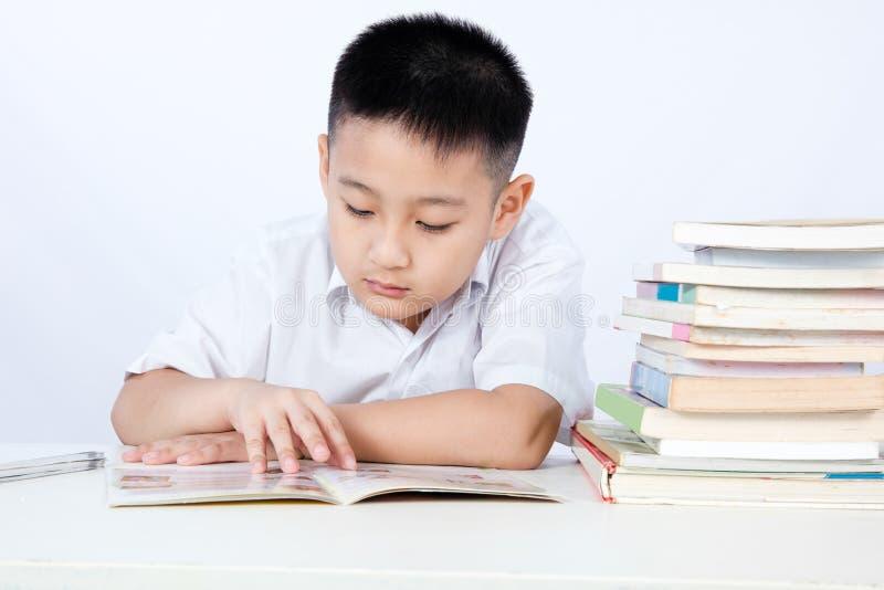 Estudiante que lleva Uniform Reading Textboo de Little Boy del chino asiático imagenes de archivo