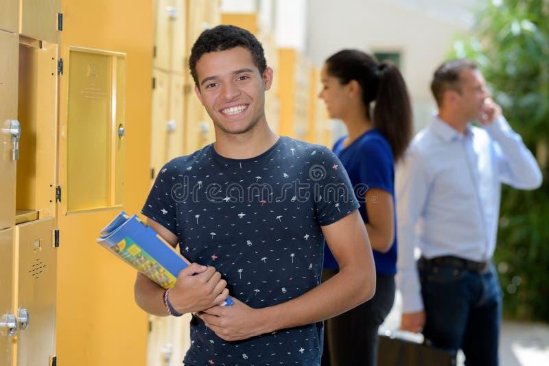 Estudiante que mantiene el libro armario en universidad imágenes de archivo libres de regalías