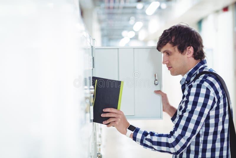 Estudiante que mantiene su libro el armario imágenes de archivo libres de regalías