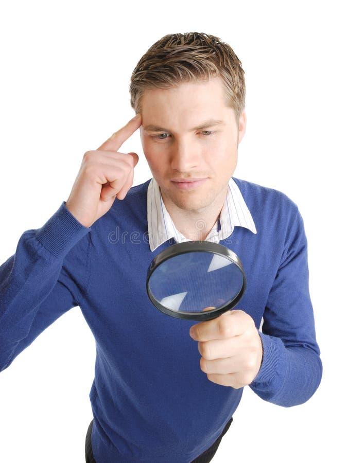 Estudiante que mira a través de una lupa imagenes de archivo
