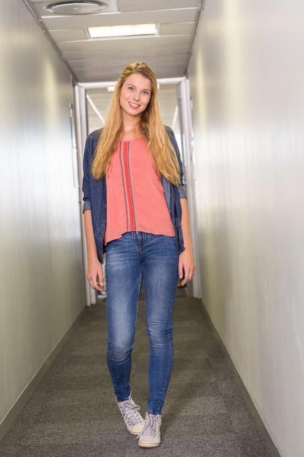 Estudiante que se coloca en el pasillo de la universidad imagen de archivo libre de regalías