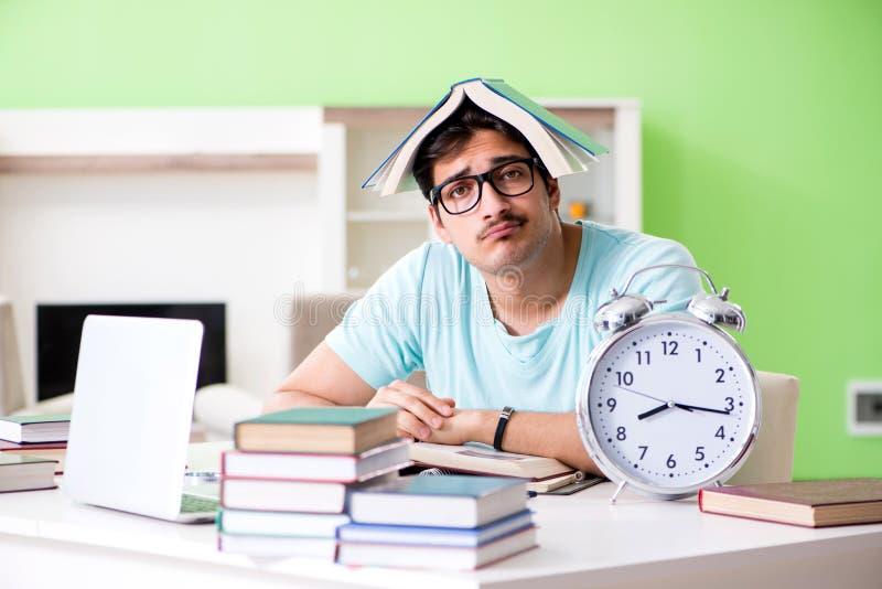 Estudiante que se prepara para los managemen de los exámenes de la universidad en casa a tiempo imagen de archivo libre de regalías