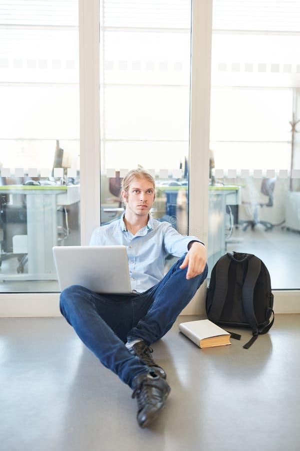 Estudiante que se sienta con la computadora portátil imagen de archivo libre de regalías