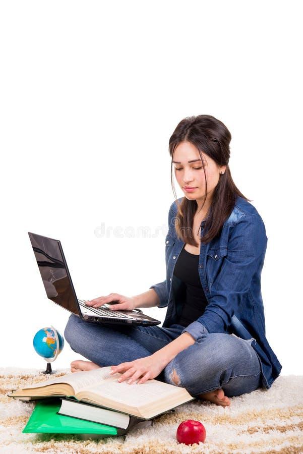 Estudiante que se sienta en la alfombra con los libros y el ordenador portátil foto de archivo