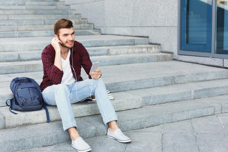 Estudiante que se sienta en las escaleras y que usa smartphone foto de archivo