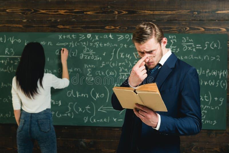 Estudiante que soluciona la ecuación en el tablero Profesor joven con la cerda corta que ajusta los vidrios mientras que lee un a foto de archivo libre de regalías