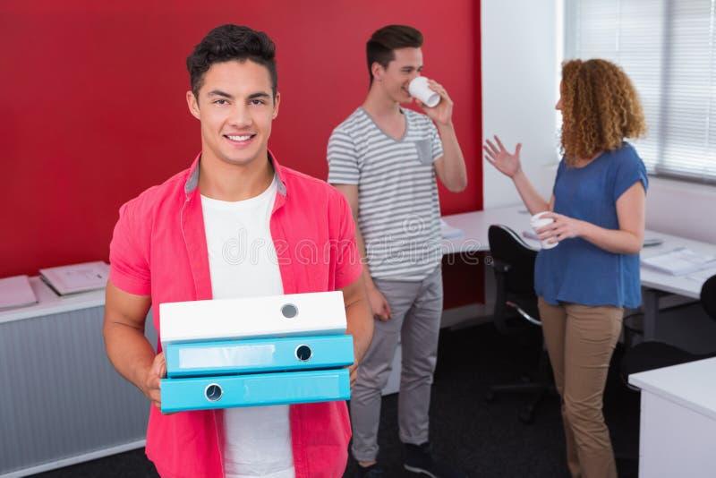Estudiante que sostiene la pila de carpeta de anillo cerca de compañeros de clase con café imágenes de archivo libres de regalías