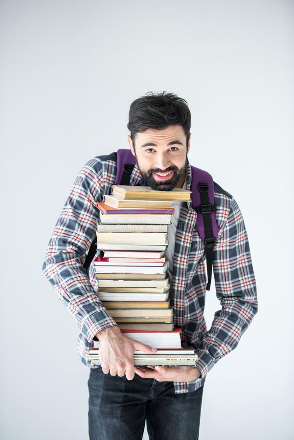 Estudiante que sostiene la pila de libros en blanco con el espacio de la copia imágenes de archivo libres de regalías