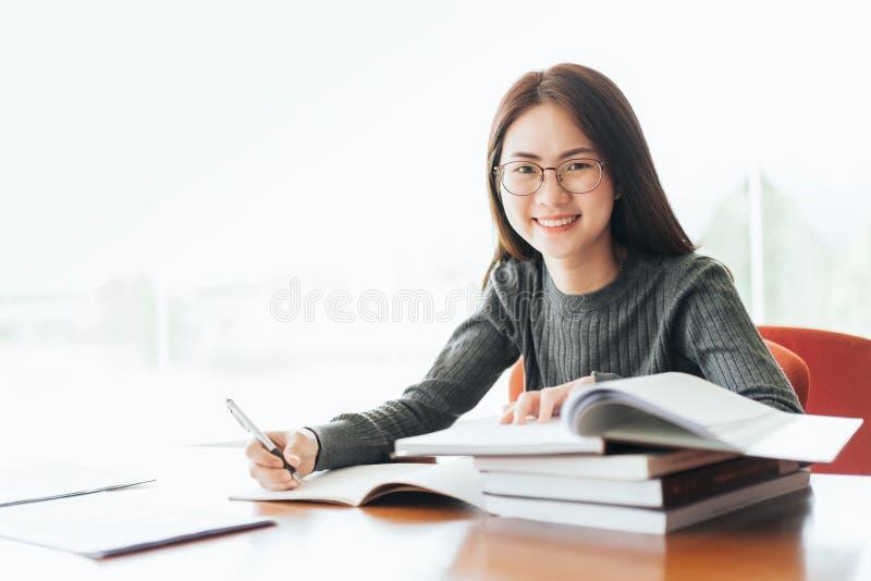 Estudiante que toma notas de un libro en la biblioteca, mujer asiática joven que se sienta en la tabla que hace asignaciones en b foto de archivo