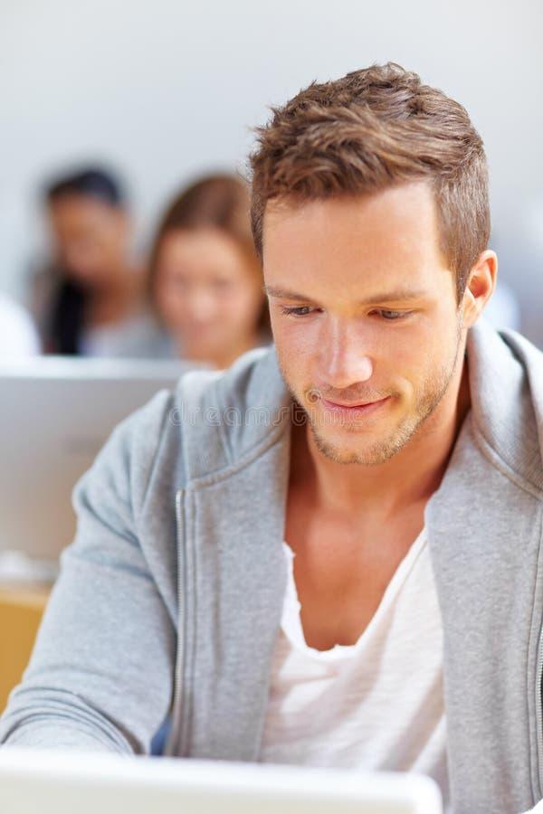 Estudiante que trabaja en la computadora portátil foto de archivo