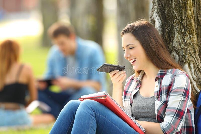 Estudiante que usa el reconocimiento vocal con un teléfono imagen de archivo