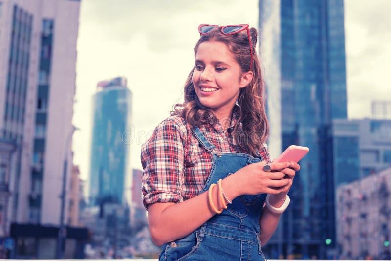 Estudiante rizado que sostiene su teléfono rosado mientras que escribe a mensaje su novio imagenes de archivo