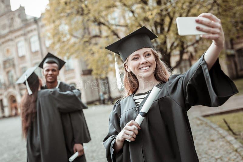 Estudiante rubio encantado positivo que hace la foto del selfie fotos de archivo