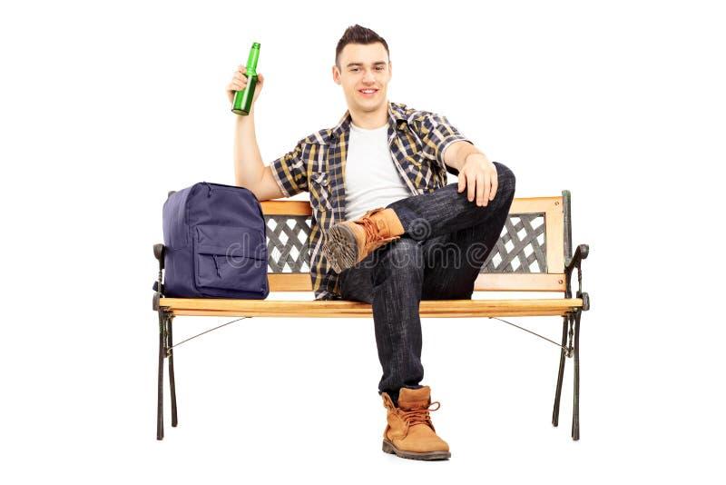 Estudiante satisfecho joven que se sienta en un banco y una cerveza de consumición fotos de archivo