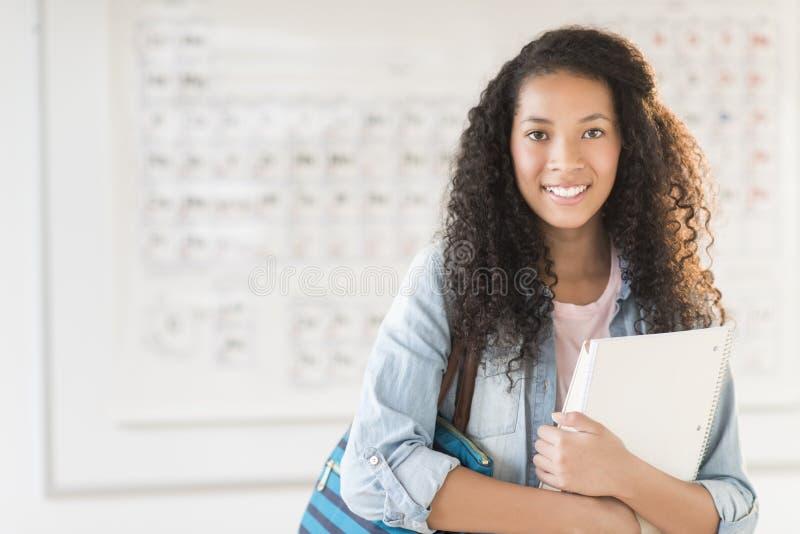 Estudiante With Shoulder Bag y libros en clase de química foto de archivo