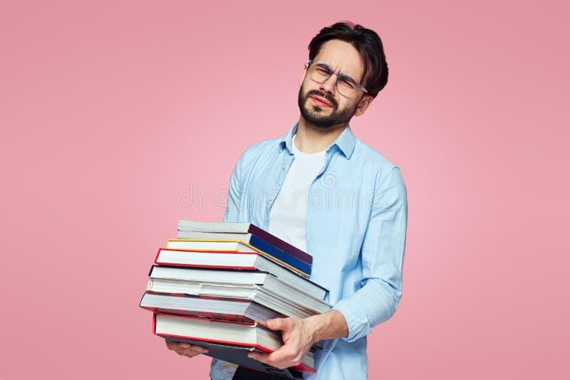 Estudiante sin afeitar con una cara cansada que sostiene un manojo de libros y que se prepara para sus exámenes próximos, aislada foto de archivo