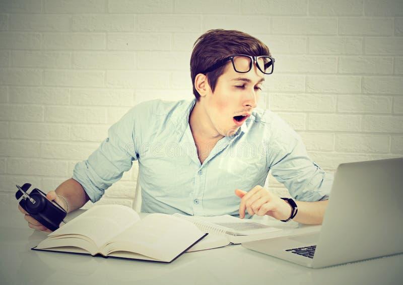 Estudiante soñoliento que se prepara para los exámenes de la escuela que bostezan fotos de archivo libres de regalías