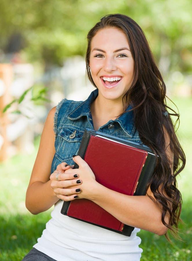 Estudiante sonriente atractivo de la chica joven de la raza mixta con los libros de escuela foto de archivo libre de regalías