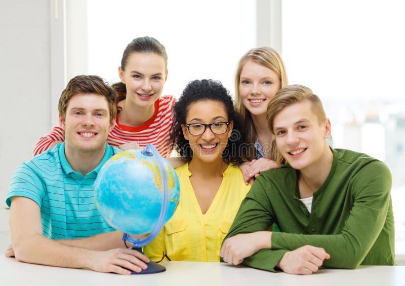 Estudiante sonriente cinco con el globo de la tierra en la escuela foto de archivo