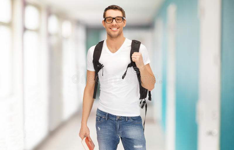 Estudiante sonriente con la mochila y el libro imagenes de archivo
