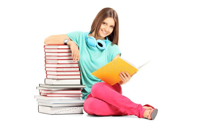 Estudiante sonriente con los auriculares que presentan cerca de muchos libros foto de archivo libre de regalías