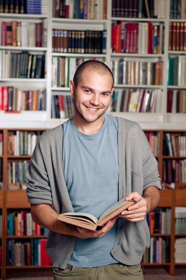 Estudiante sonriente en biblioteca imagen de archivo