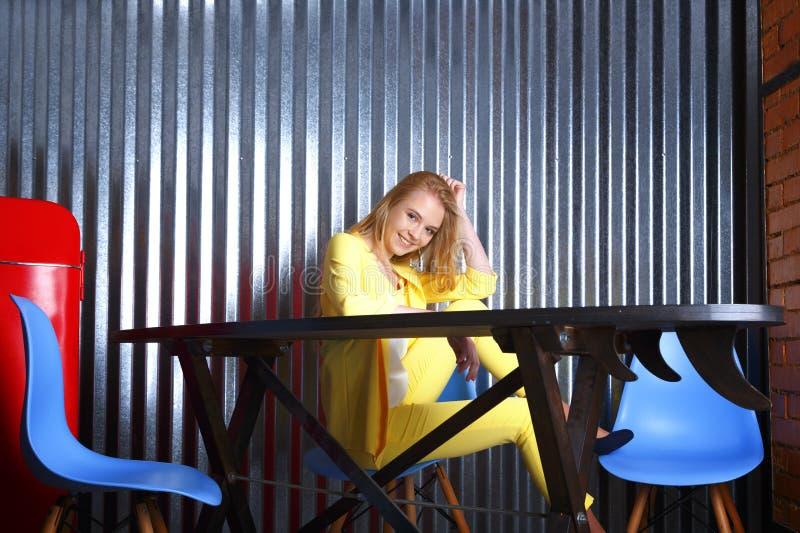 Estudiante sonriente en el traje amarillo que se sienta en la tabla Oficina de Coworking, café moderno del desván, lugar de traba fotos de archivo libres de regalías