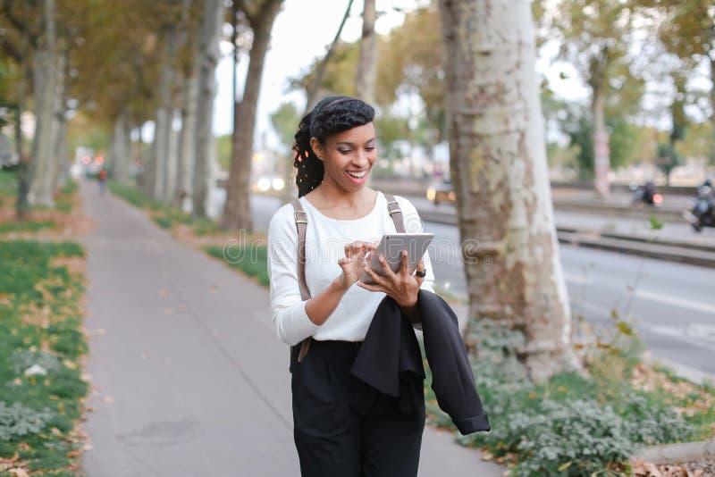 Estudiante sonriente femenino negro que usa la tableta y caminando en la calle con los árboles imagen de archivo