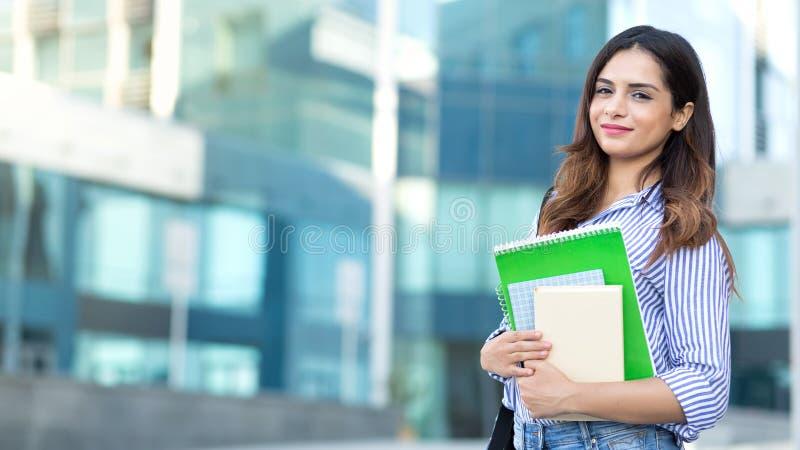 Estudiante sonriente joven que sostiene los libros, estudio, educación, conocimiento, concepto de la meta fotos de archivo libres de regalías