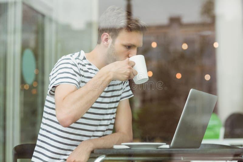 Estudiante sonriente que bebe la bebida caliente imagenes de archivo