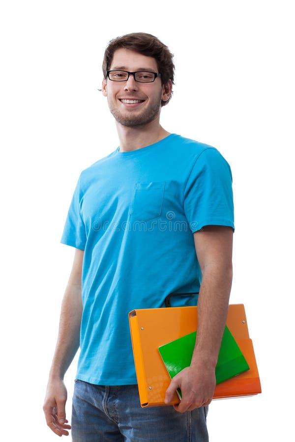 Estudiante sonriente que guarda la carpeta fotos de archivo libres de regalías