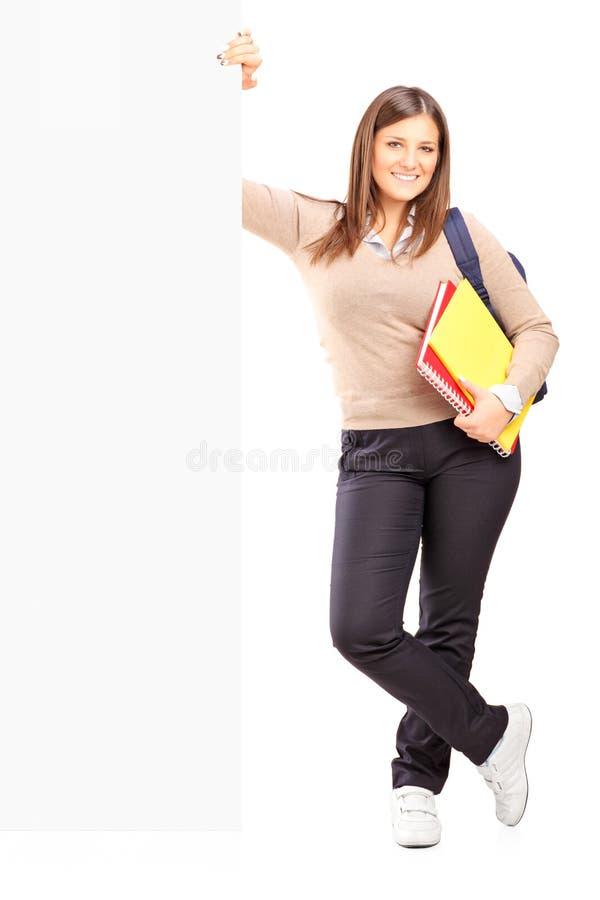 Estudiante sonriente que se coloca al lado de una cartelera fotos de archivo libres de regalías