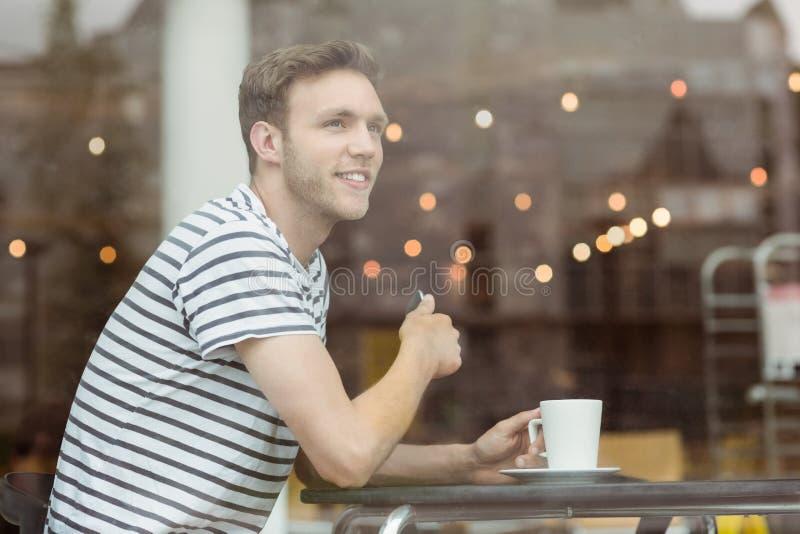 Estudiante sonriente que se sienta con una bebida caliente fotografía de archivo