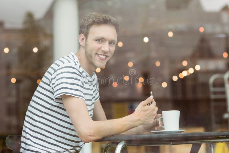 Estudiante sonriente que se sienta con una bebida caliente fotografía de archivo libre de regalías