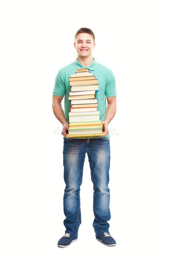 Estudiante sonriente que sostiene la pila grande de libros imágenes de archivo libres de regalías