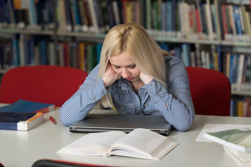 Estudiante subrayado Doing Her Homework en el escritorio foto de archivo libre de regalías