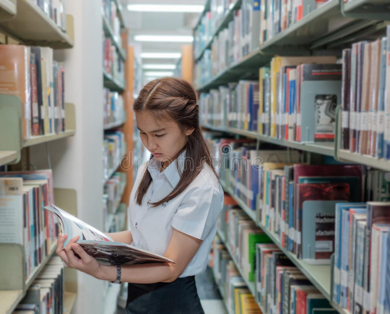 Estudiante tailandesa en uniforme que lee un libro en biblioteca imagenes de archivo