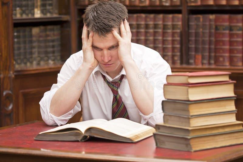 Estudiante tensionado con una pila de libros a leer imagenes de archivo
