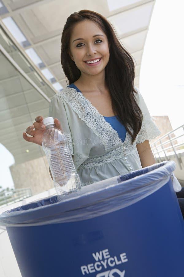 Estudiante Throwing Plastic Bottle en cubo de basura imagen de archivo libre de regalías