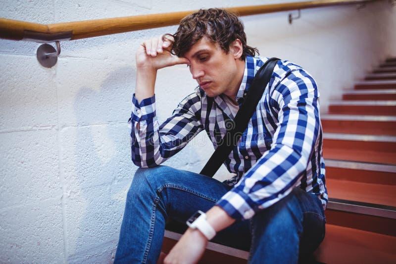 Estudiante trastornado que se sienta en escalera foto de archivo libre de regalías