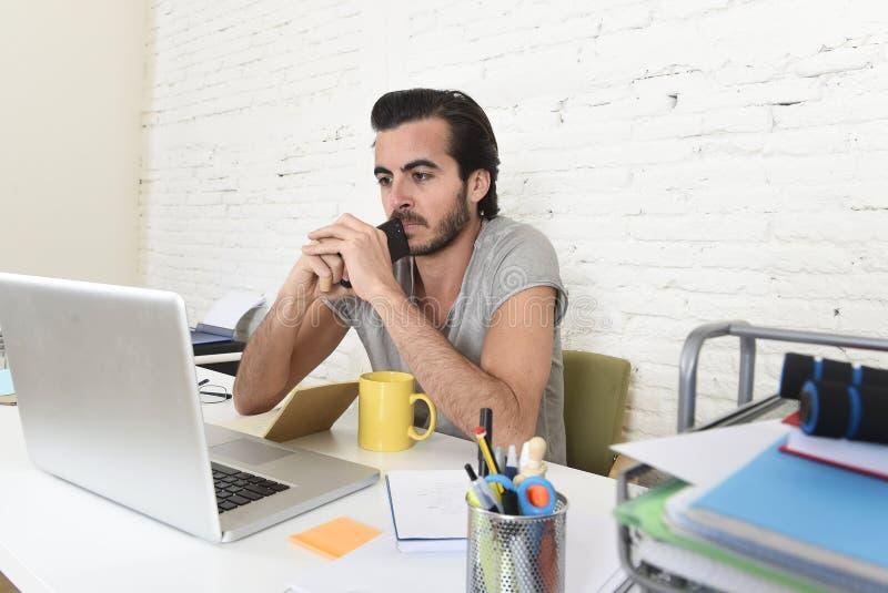 Estudiante u hombre de negocios moderno joven del estilo del inconformista que trabaja llevando a cabo el pensamiento del teléfon foto de archivo libre de regalías