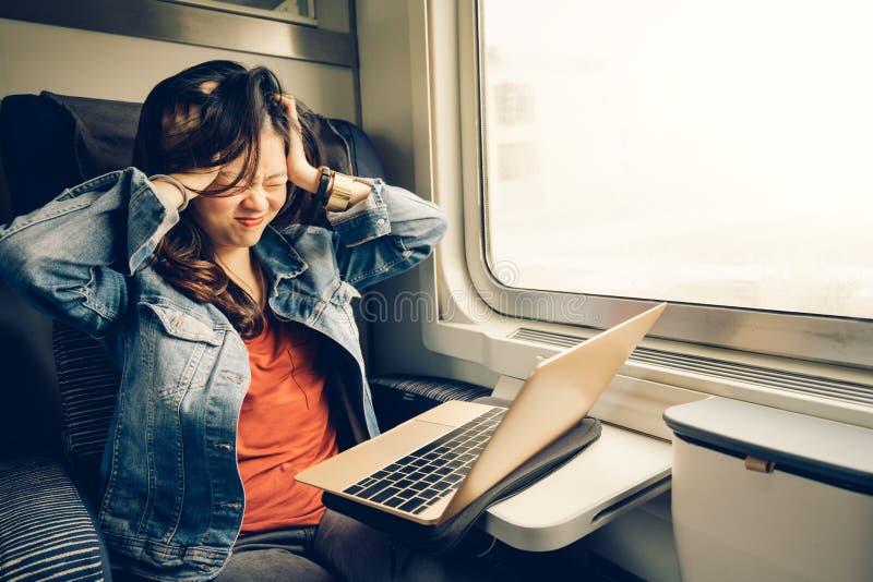 Estudiante universitaria asiática frustrada con el ordenador portátil en el tren, tono ligero caliente, con el espacio de la copi fotografía de archivo libre de regalías