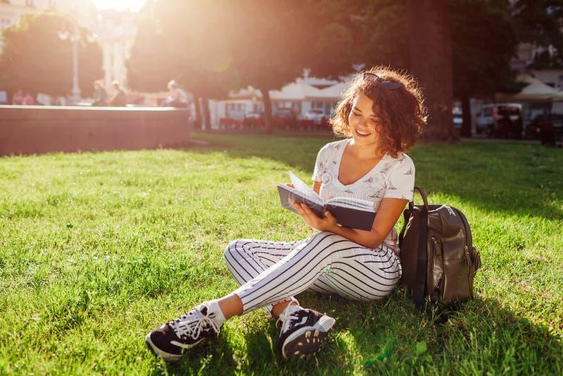 Estudiante universitaria hermosa que lee un libro en parque del campus Estudiante de mujer feliz que aprende al aire libre fotografía de archivo libre de regalías
