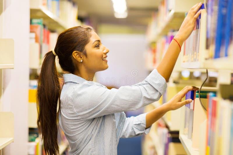Estudiante universitaria que busca para el libro imagen de archivo libre de regalías