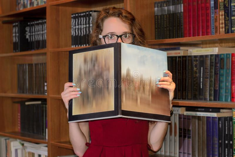 Estudiante universitaria que oculta detrás del libro imágenes de archivo libres de regalías