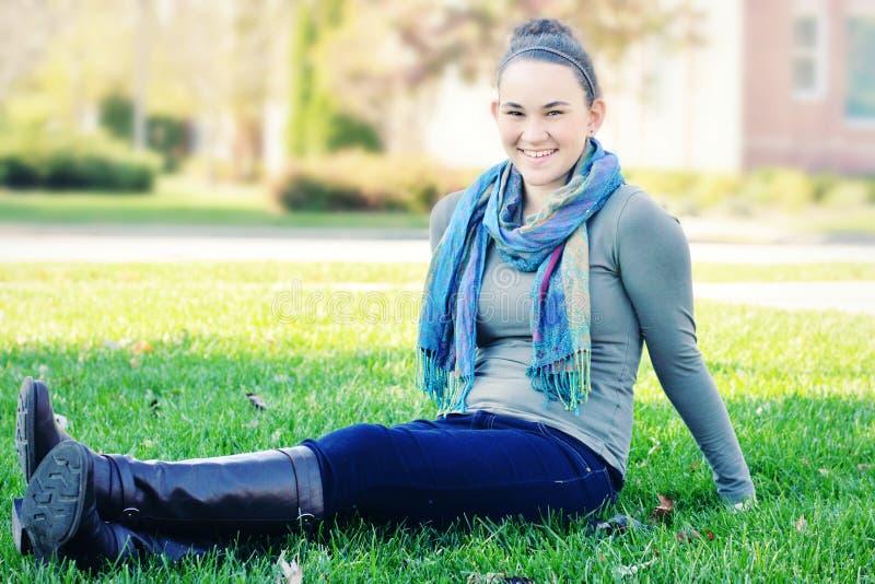 Estudiante universitaria que se sienta en césped foto de archivo